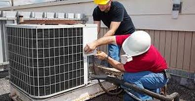 Two men fixing air conditioner