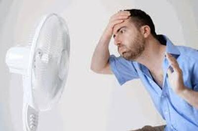 Man overheating with fan